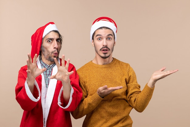 Vista frontale due uomini confusi uno che mostra qualcosa su sfondo beige isolato