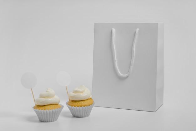Vista frontale di due cupcakes con sacchetto di imballaggio