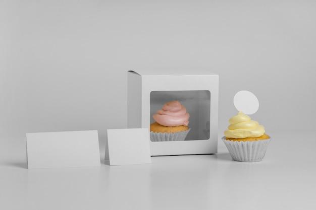 Vista frontale di due cupcakes con scatola di imballaggio e carte vuote