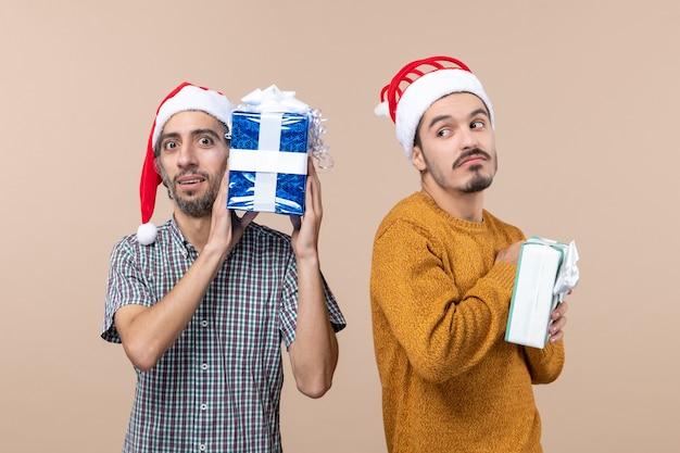 Вид спереди двух любопытных парней в шляпах санта-клауса и думающих о рождественских подарках на бежевом изолированном фоне