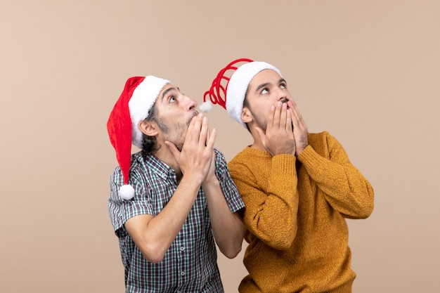 Vista frontale due uomini curiosi con cappelli di babbo natale guardando qualcosa con grande interesse su sfondo isolato