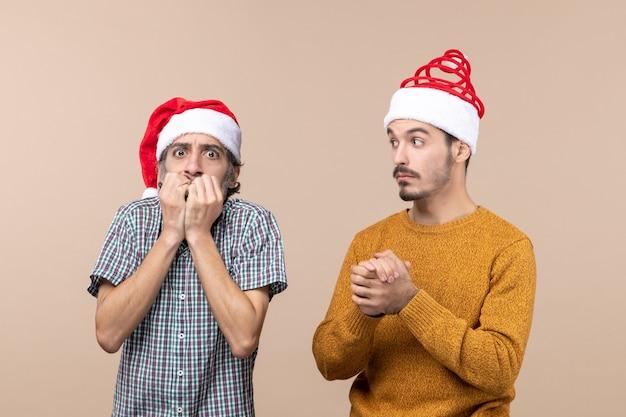베이지 색 격리 된 배경에 자신의 마우스에 손을 댔을 산타 모자와 전면보기 두 우울 사람
