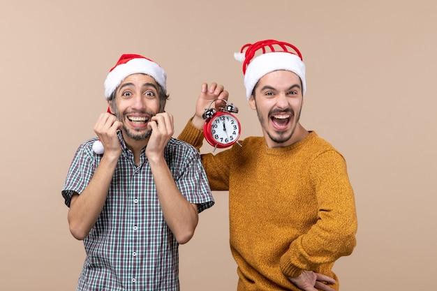 Vista frontale due uomini euforici uno in possesso di una sveglia in piedi su sfondo beige isolato