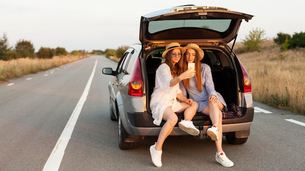 Front view of two female friends taking selfie in the car trunk