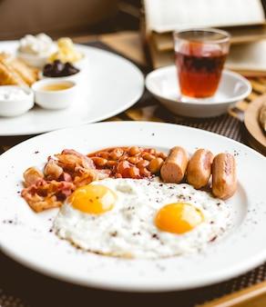 Вид спереди два жареных яйца с сосисками, фасолью и беконом на тарелке