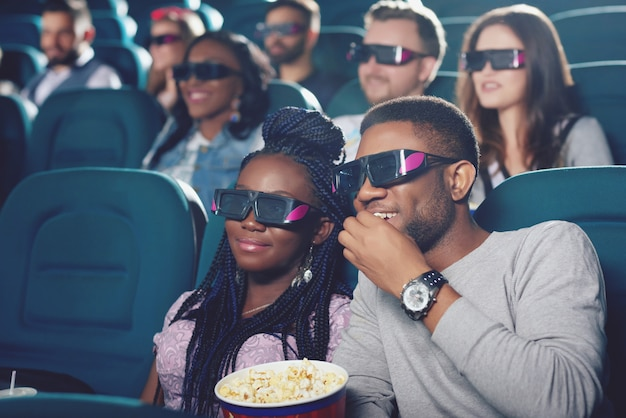 Front view of two friends in 3d glasses sitting in modern cinema hall eating popcorn and watching funny movie.