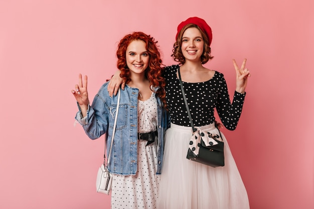 Front view of two friends embracing on pink background. studio shot of smiling girls showing peace signs.