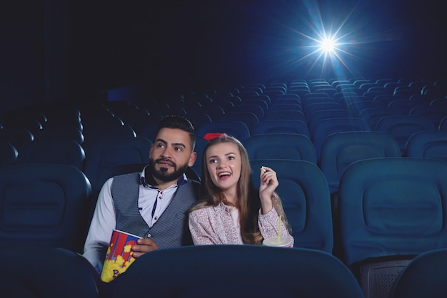 Front view of two friends embracing and sitting alone in modern cinema hall, watching funny movie.