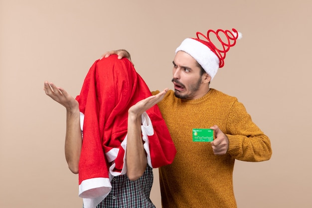 Front view two friends one holding credit card while touching his head and the other covering his head with santa coat on beige isolated background