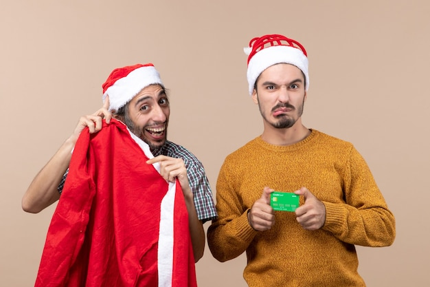 Front view two friends one holding santa coat and the other with credit card looking at camera on beige isolated background