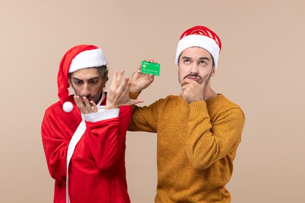 Front view two friends one with santa coat looking at his hand and the other holding card on beige isolated background