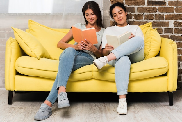 Front view of two friends relaxing at home on couch with books