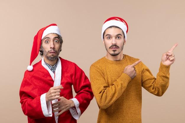 혼란스러운 산타 모자와 베이지 색 격리 된 배경에 다른 표시 방향으로 전면보기 두 친구