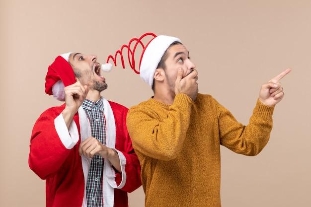 Vista frontale due amici con cappelli di babbo natale uno che cerca di catturare cappelli pompon e l'altro che mostra la direzione su sfondo beige isolato