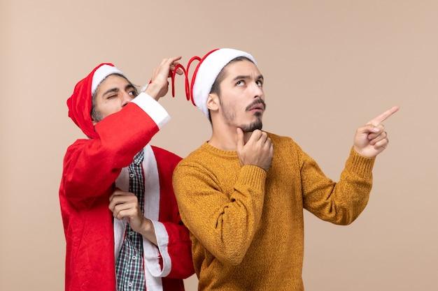 Вид спереди двух друзей в шляпах санта-клауса, один пытается держать шляпы с помпоном, а другой показывает направление на бежевом изолированном фоне