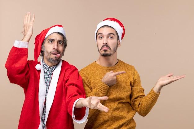 Vista frontale due uomini divertenti uno che mostra la sua lingua e l'altro che mostra qualcosa su sfondo beige isolato