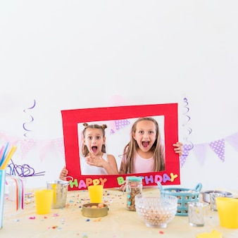 Front view of two girls holding birthday text photo frame behind table at party