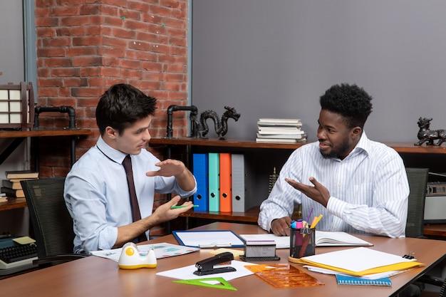 Вид спереди двух радостных бизнесменов, сидящих за столом и обсуждающих проект в офисе