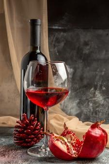 Vista frontale di due bicchieri e bottiglia con delizioso vino rosso secco e cono di conifere di melograno aperto su sfondo di ghiaccio
