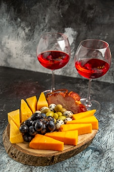 Vista frontale di due bicchieri di vino rosso secco e snack su sfondo grigio