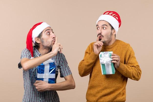 Vista frontale due ragazzi che fanno segno di shh e che tengono i regali su fondo isolato beige