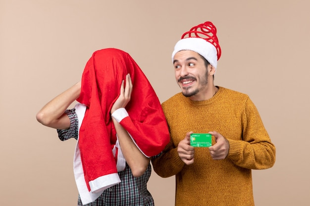 Front view two guys one holding credit card and the other covering his head with santa coat on beige isolated background