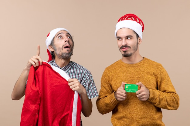 Front view two guys one holding santa coat and looking at high and the other with credit card looking at his friend on beige isolated background