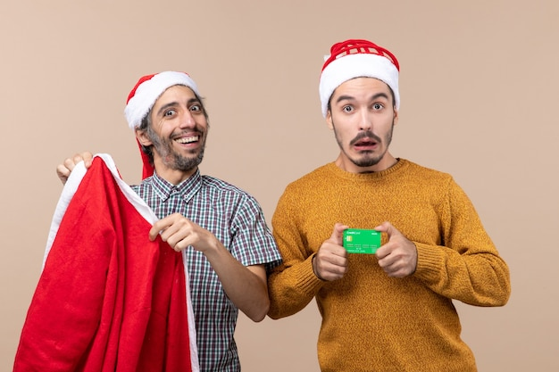 Front view two guys one holding santa coat and the other with credit card looking at camera on beige isolated background