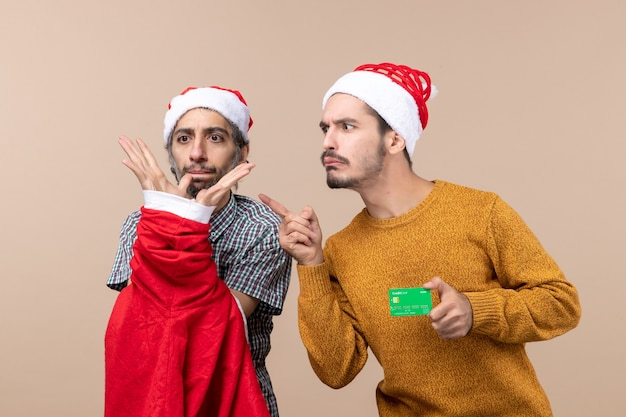 Front view two guys one holding santa coat and the other with credit card looking at something on beige isolated background
