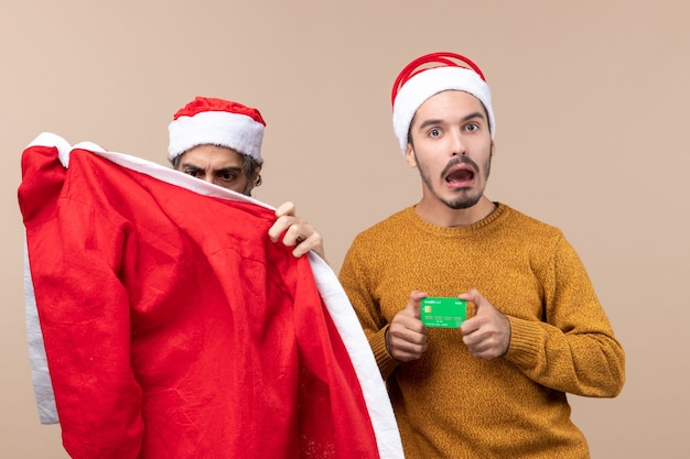 Front view two guys one looking at santa coat and the other with credit card on beige isolated background