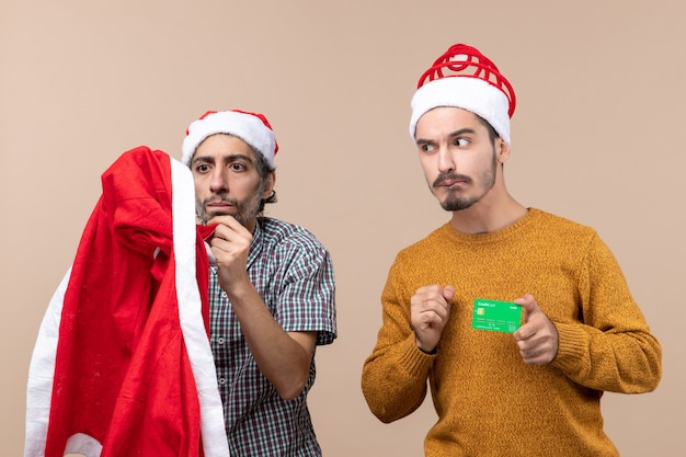 Front view two guys one looking at santa coat and the other with credit card looking at him on beige isolated background