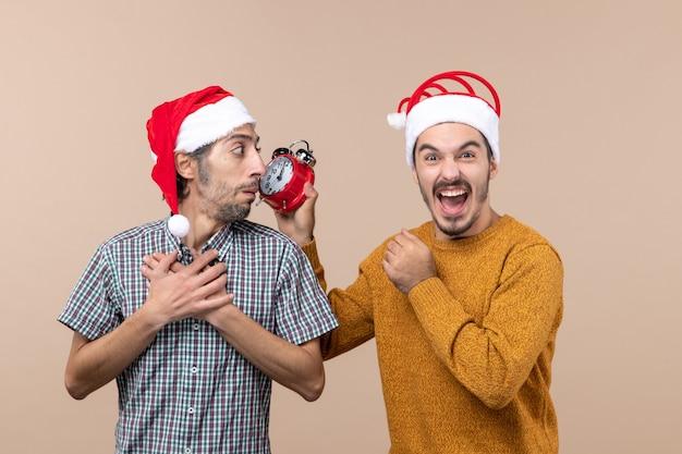 Vista frontale due ragazzi uno che mette le mani sul petto e l'altro che tiene una sveglia su sfondo beige isolato