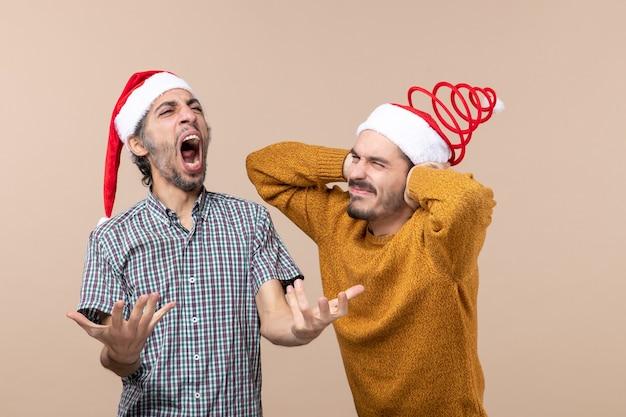 Vista frontale due ragazzi uno che canta ad alta voce e l'altro si coprono le orecchie con le mani su sfondo beige isolato