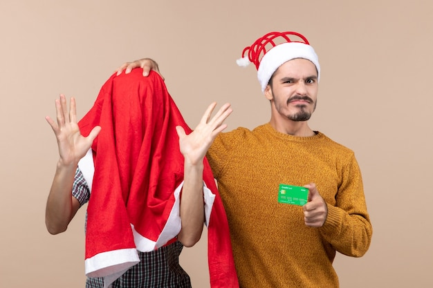 Front view two guys one with santa coat over his head the other holding a card while touching his friends head on beige isolated background