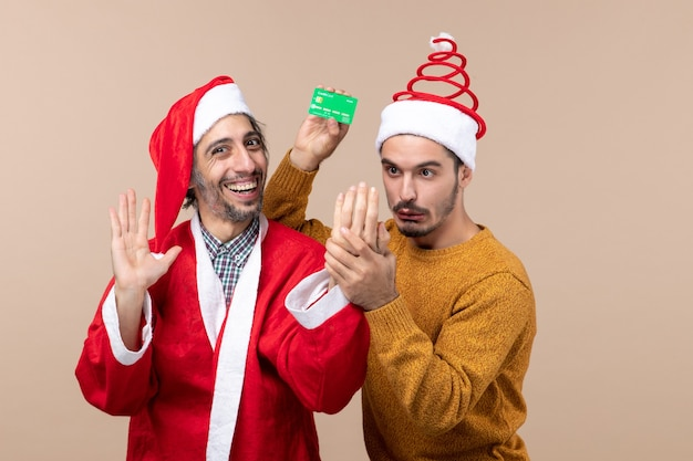 Front view two guys one with santa coat laughing and the other holding card on beige isolated background