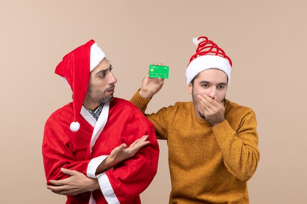 Front view two guys one with santa coat and the other with credit card closing his nose on beige isolated background