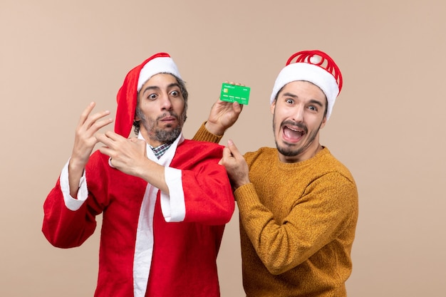 Front view two guys one with santa coat and the other with credit card confusing on beige isolated background