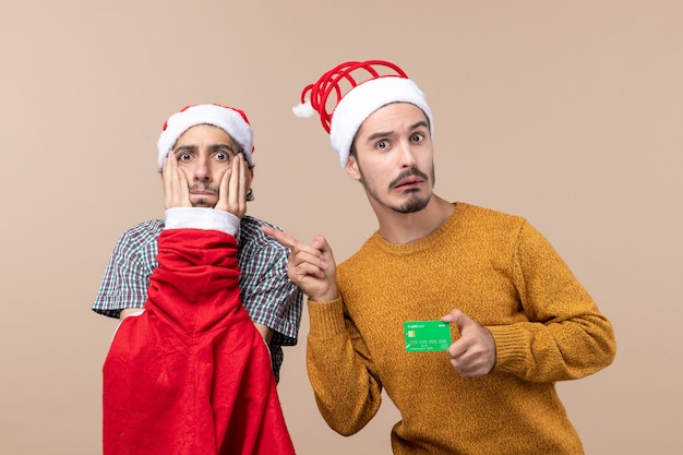 Front view two guys one with santa coat putting hands on his face and the other with credit card on beige isolated background