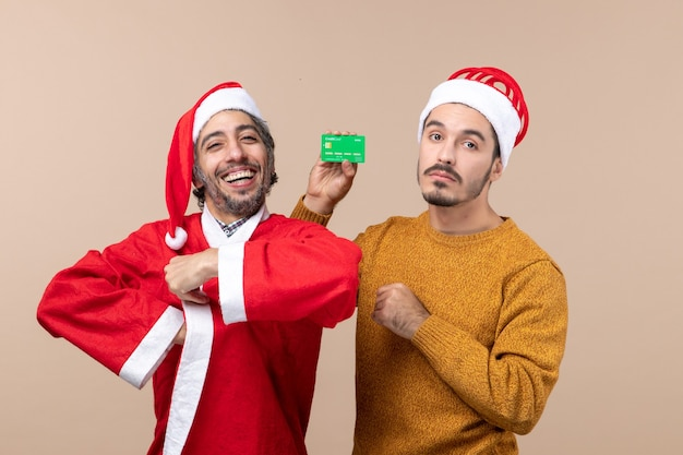Front view two guys one with santa coat smiling and the other with credit card looking at camera on beige isolated background