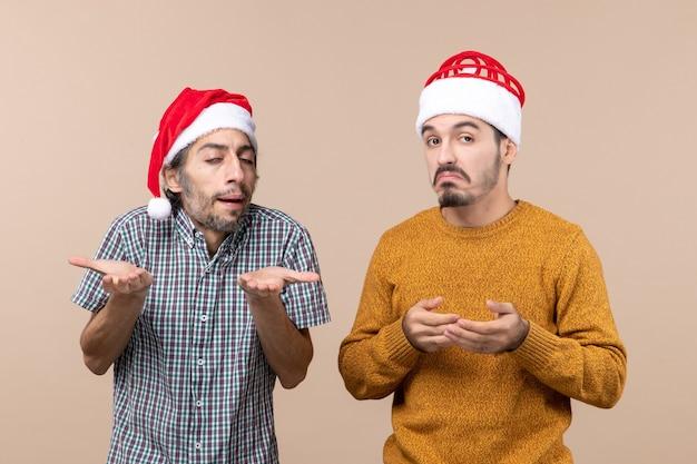 베이지 색 격리 된 배경에 혼란 산타 모자와 전면보기 두 남자