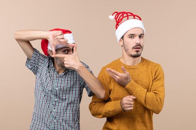 Вид спереди двух парней в шляпах санта-клауса, один делает знак камеры руками, а другой показывает его на бежевом изолированном фоне