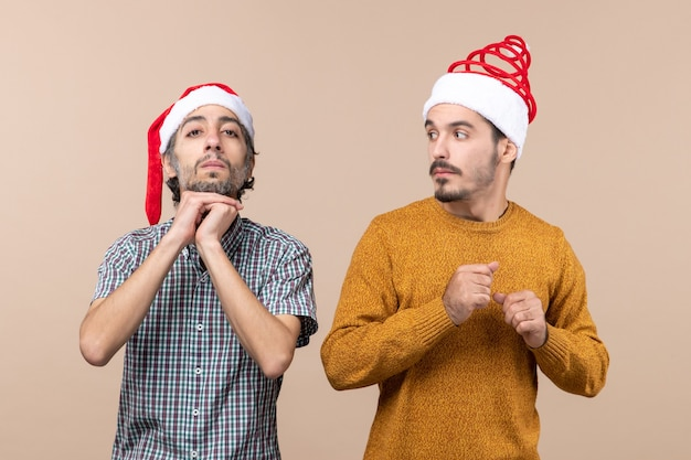 Vista frontale due ragazzi con cappelli di babbo natale uno che mette le mani sulla mascella, l'altro lo guarda su sfondo beige isolato