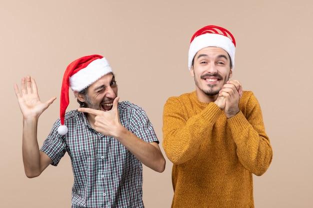 그의 손을 보여주는 산타 모자와 전면보기 두 사람이 다른 닫힌 눈 베이지 색 격리 된 배경으로 소원