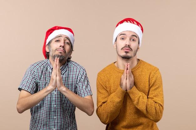 Vista frontale due ragazzi con cappelli di natale che mendicano su sfondo beige isolato