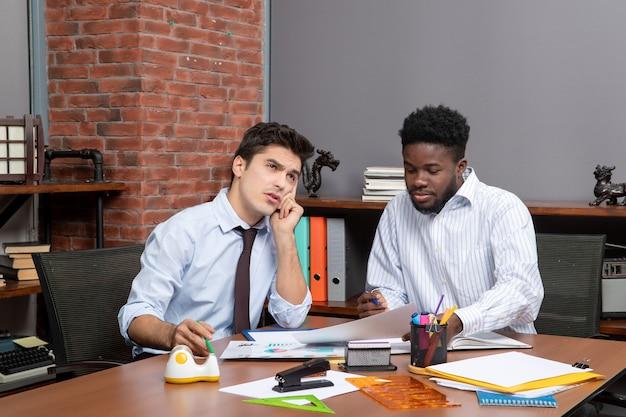 一緒に働くことを満足させるフォーマルウェアの2人のハンサムなビジネスマンの正面図