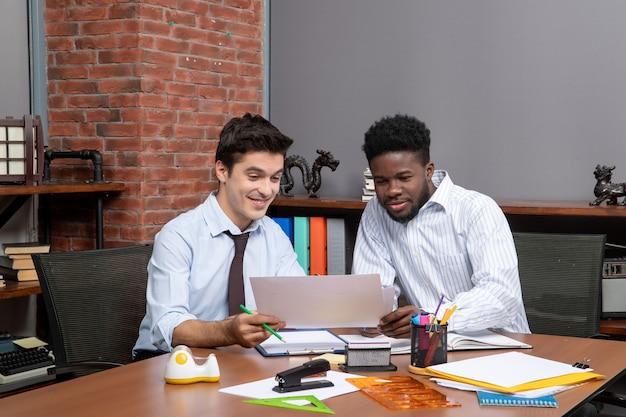 正面図オフィスで一緒に働くことに満足している2人の幸せなビジネスマン