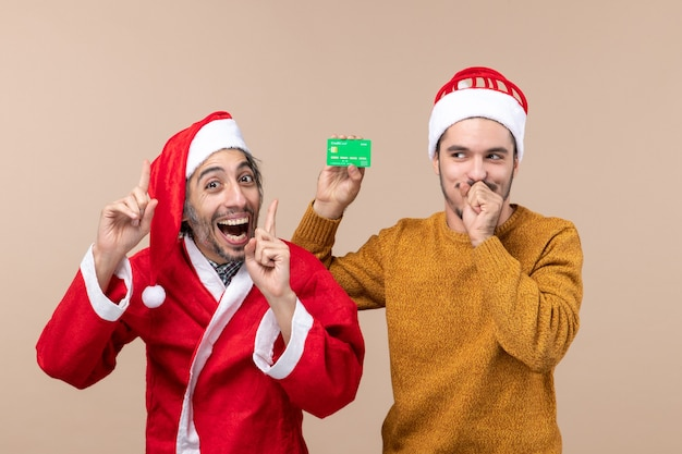 Front view two happy guys one with santa coat and the other with credit card closing his mouth on beige isolated background