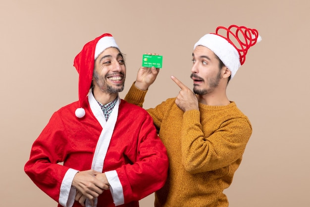 Front view two happy guys one with santa coat and the other with credit card looking at it on beige isolated background