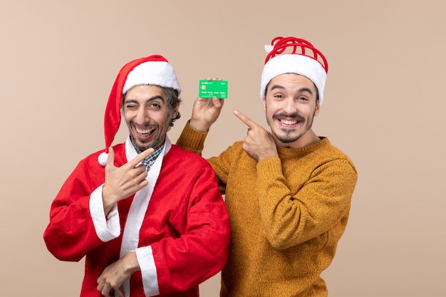 Front view two happy guys one with santa coat and the other with credit card smiling on beige isolated background