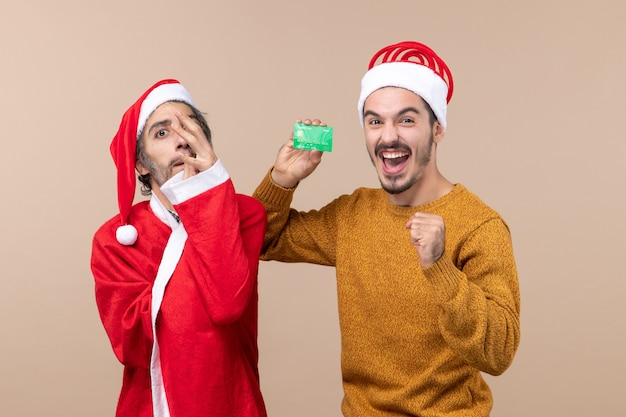 Front view two happy guys one with santa coat putting hand on his face and the other holding card on beige isolated background